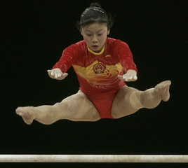 Zhou Zhuoru of China competes in the uneven bars during the gymnastics women's team event at the 15th Asian Games in Doha