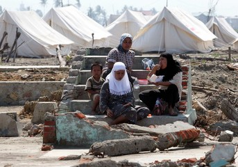 An Acehnese family rests while clearing land destroyed by last December's tsunami in Aceh.