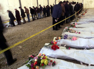 Grieving relatives file past the remains of 44 ethnic Albanians who were killed in Kosovo in 1999, a..