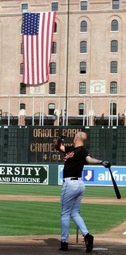 ORIOLES CAL RIPKEN HITS OFF TEE WITH FLAG IN BACKGROUND.