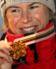 Czech Republic's Neumannova shows her gold medal after she won the women 10km free individual cross ...