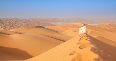 arab man in traditional outfit sitting over a Dune in arabian desert and enjoying the peaceful landscape of the empty quarter Wall mural