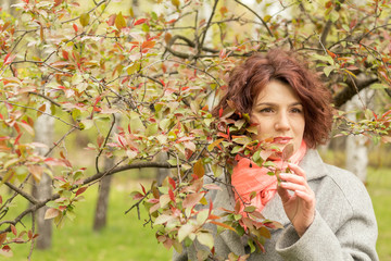 Pretty romantic young red head woman with apple branches red leaves in spring park. Spring trees background. Portrait close up.