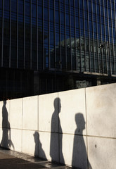 The shadows of people are cast on a wall at Canary Wharf financial district