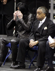 Michael Jackson wipes his eyes as he sits with the Rev. Al Sharpton during the public funeral service for singer James Brown at the James Brown Arena in Augusta.
