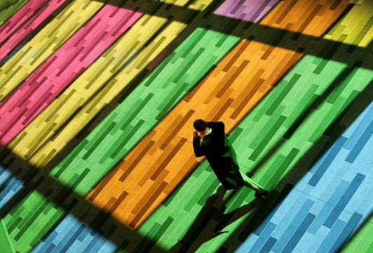 A pedestrian walks through light streaming through colored windows at the Montreal convention center..