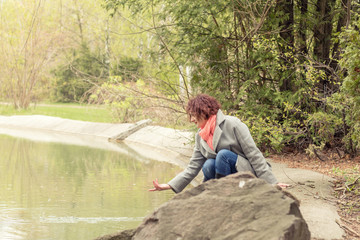 Pretty romantic young red head woman sitting close to the pond in spring park. Spring trees background.