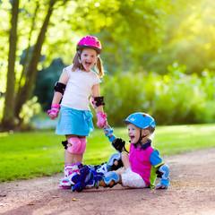 Kids roller skating in summer park