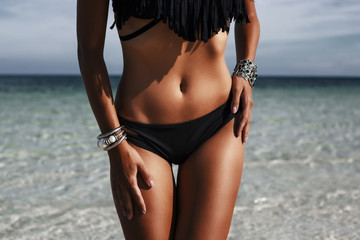 Close-up of an ideal fitness body of a luxurious girl on the beach, sexy black bikini, perfect bronze tan skin, Fashionable silver accessories,  low key photo, Radiant skin, Fashion glamor, life style