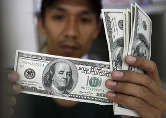 Worker inspects hundred-dollar bills before exchanging it for Philippine pesos inside a money changer in Manila