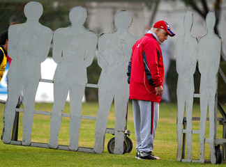 Nelson Acosta, coach of Chilean soccer team, stands next to a wall of human silhouettes during a ...