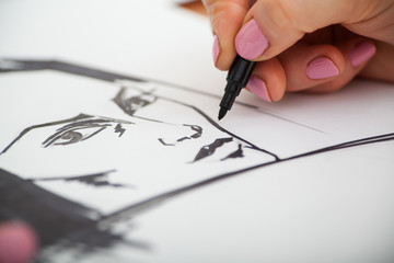 Closeup of drawing woman's portrait at the desk