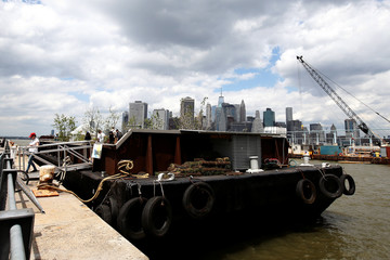 A woman walks off a floating barge, which is planted with fruit trees as part of the Swale project called a collaborative floating forest, in the East River in the Brooklyn borough of New York