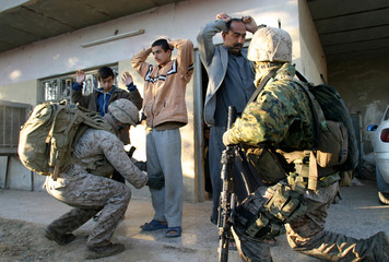 US Marines search villagers during operations south of Baghdad.