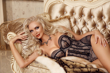 Fashion interior photo of gorgeous sexy blond girl in lingerie corset lying on luxury modern sofa in golden bedroom. Beauty glamour style portrait.