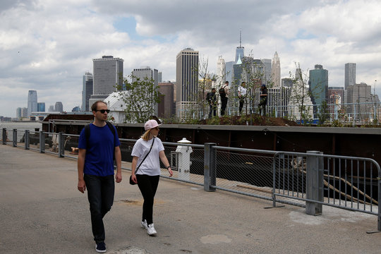 People walk past a floating barge, which is planted with fruit trees, with the Manhattan skyline in the background, as part of the Swale project called a collaborative floating forest, in the East River in the Brooklyn borough of New York
