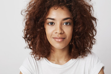Close up portrait of beautiful african girl with big eyes smiling looking at camera with a grin feeling confident and calm, being compelling and attractive.