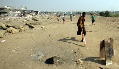 Children play cricket at Nehru Nagar slum in Mumbai