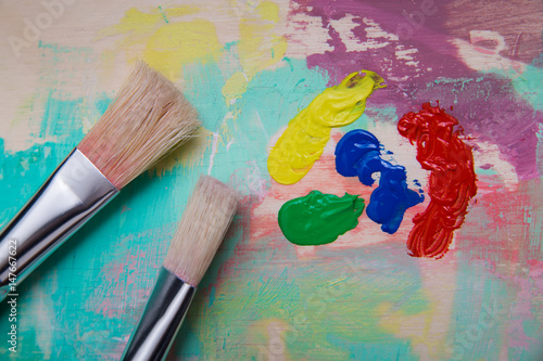 brushes on the used pallet paint spots yellow green blue red top view and closeup photo. Black Bedroom Furniture Sets. Home Design Ideas