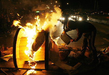 Students burn objects along a road during protests in Valparaiso city, about 120 km northwest of Santiago