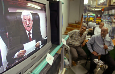 Palestinian men watch televised speech by Palestinian President Abbas in Gaza.