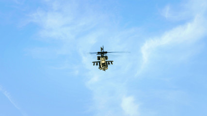 Helicopter flying in blue cloudy sky