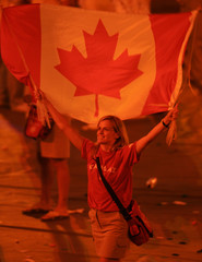 An athlete from Canada waves her national flag during the closing ceremony of the Athens 2004 ...