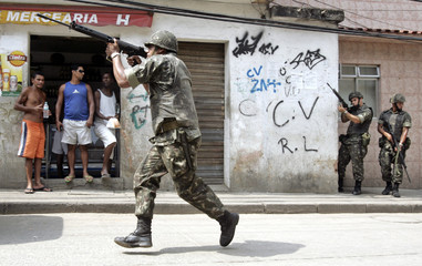 Brazilian army soldier runs during an operation to search for weapons in Rio de Janeiro