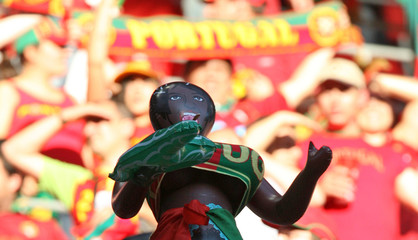 An Angola fan holds a blow-up doll in the stands before their Group D World Cup 2006 soccer match against Portugal in Cologne
