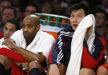 New Jersey Nets Yi Jianlian of China and Vince Carter sit on the bench during the fourth quarter of their NBA basketball game against the Los Angeles Lakers in Los Angeles