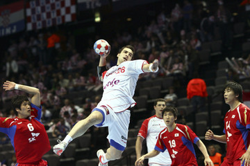 Spain's Pasarin attempts to score between South Korea's defensive players during their Men's World Handball Championship preliminary Group B match in Split
