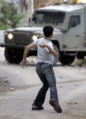 A Palestinian youth throws a stone at an Israeli military vehicle during a military operation in the West Bank village of Qabatiya