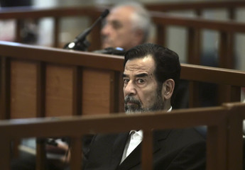 Former Iraqi President Saddam Hussein listens to prosecutors' statements during his trial in Baghdad's heavily fortified Green Zone