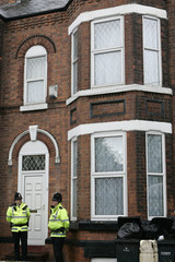 Police officers stand outside a house in Manchester  following a series of anti-terrorism raids across the north-west of England