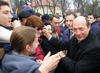 Romanian President Basescu is greeted by Bucharest residents after a military parade celebrating Romania's National Day