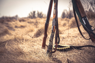 Foto op Aluminium Jacht Hunting scene with hunting shotguns and ammunition belt on dry grass in rural field during hunting season as hunting background