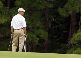 U.S. President Barack Obama pauses at the edge of a green while golfing at Mink Meadows golf course in Tisbury