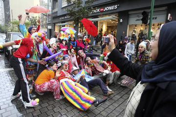 Activists dressed as clowns block Hamra street as a woman photographs them during a parade in Beirut