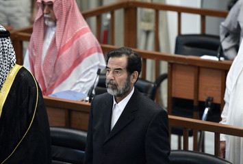 Former Iraqi President Saddam Hussein stands during his trial in Baghdad