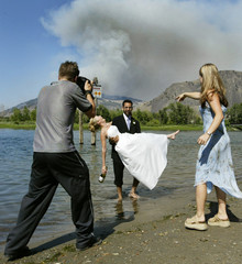 COUPLE POSES FOR WEDDING PHOTOS WITH WILDFIRE RAGING IN BACKGROUND.