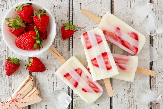 Group of homemade strawberry vanilla popsicles on a rustic white wood background