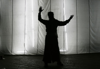 A member of Iraqi national folklore dancing troupe is silhouetted behind a curtain in Baghdad