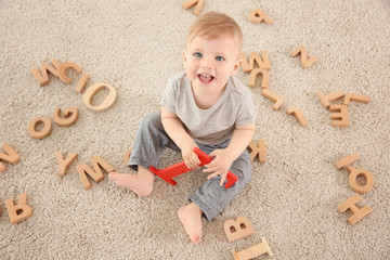Cute little child with wooden letters sitting on carpet at home