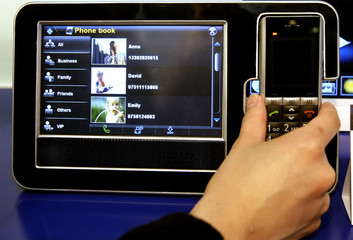 A woman holds a mobile Touch Frame from Giant Electronics Ltd at GSMA Mobile World Conference in Barcelona