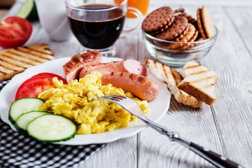 Hearty and traditional breakfast, scrambled eggs and milk with grilled pork, vegetables, tomato, cucumber, toast, juice and black coffee on a white wooden background
