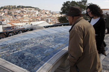 Tourists look at a tile-painting of city of Lisbon