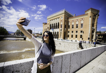Tourist Girl taking selfie for social media with smart phone smiling on summer fun travel adventure during a tour of the city