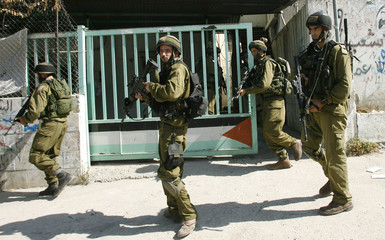 Israeli soldiers take position during a military operation in al-Ein refugee camp
