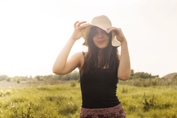Hippie girl in nature, holding hat looking at the camera