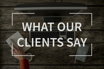 What our clients say text over top view image of office desk